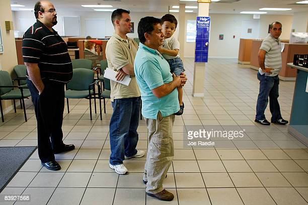 Juan Carlos Rojas holds his 2 year old son Juan Pablo Rojas as he stands in line with Jose Pineiro and Angel Morales as they look for employment help...