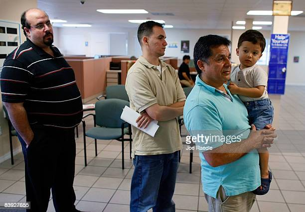 Juan Carlos Rojas holds his 2 year old son Juan Pablo Rojas as he stands in line with Jose Pineiro and Angel Morales as they look for jobs at the...