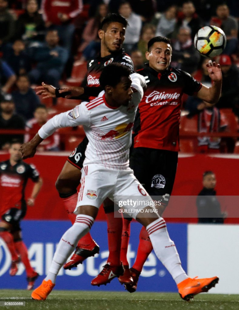 Juan Carlos Valenzuela (L) and Rubio Rubin (R) of Tijuana from Mexico vies for the ball with Michael Murillo (C) of New York from United States during the first leg of the CONCACAF Champions League quarterfinals match at Caliente Stadium in Tijuana, Mexico on March 6, 2018. /