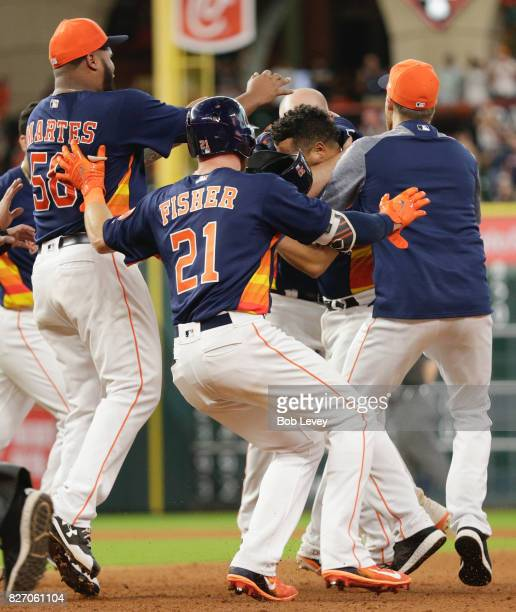 Juan Centeno of the Houston Astros is mobbed by his teammates after a hitting walkoff single aToronto Blue Jays at Minute Maid Park on August 6 2017...