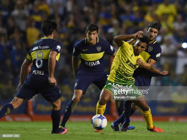 Juan Cruz Kaprof of Defensa y Justicia fights for ball with Pablo Perez Santiago Vergini and Sebastian Perez of Boca Juniors during a match between...