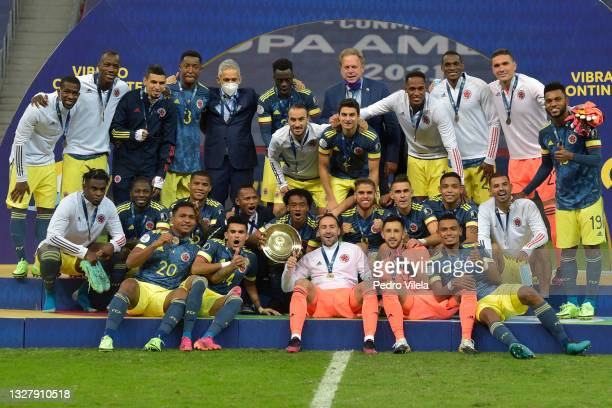 Juan Cuadrado and David Ospina of Colombia pose with the third place trophy after winning a Third Place play off match between Peru and Colombia as...