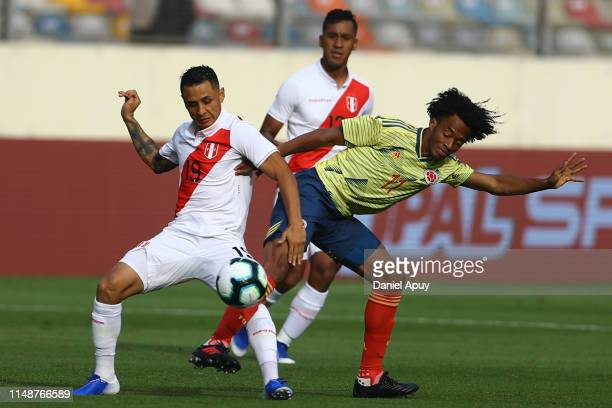 Juan Cuadrado and Yoshimar Yotun compete for the ball during a friendly match between Peru and Colombia at Estadio Monumental on June 9, 2019 in...