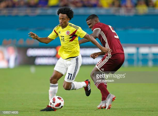 Juan Cuadrado of Colombia bring the ball past Sergio Cordova of Venezuela during the second half of an International friendly match on September 7...