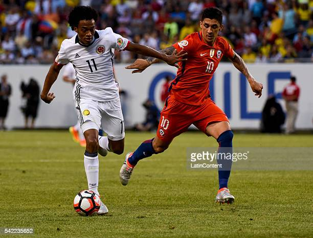 Juan Cuadrado of Colombia fights for the ball Pablo Hernandez of Chile during a Semifinal match between Colombia and Chile at Soldier Field as part...