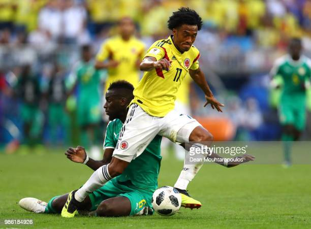 Juan Cuadrado of Colombia is challenged by Salif Sane of Senegal during the 2018 FIFA World Cup Russia group H match between Senegal and Colombia at...