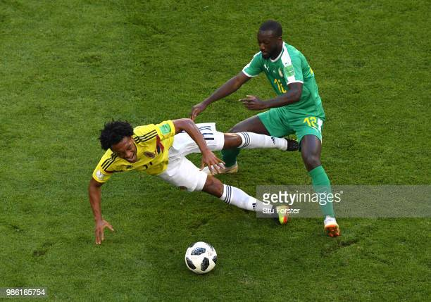 Juan Cuadrado of Colombia is challenged by Youssouf Sabaly of Senegal during the 2018 FIFA World Cup Russia group H match between Senegal and...