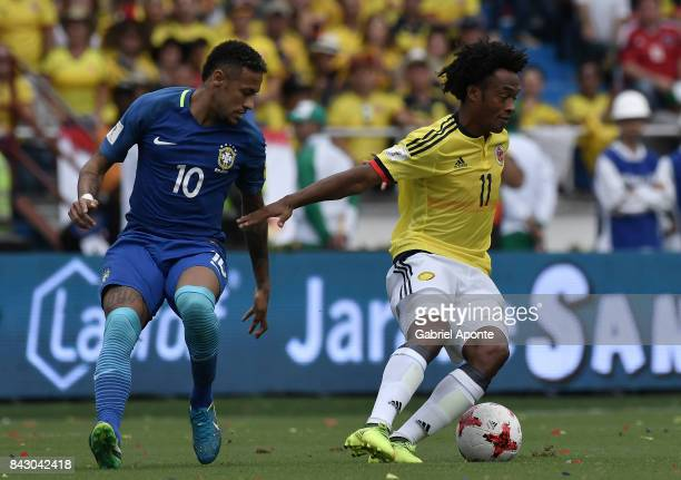 Juan Cuadrado of Colombia struggles for the ball with Neymar Jr of Brazil during a match between Colombia and Brazil as part of FIFA 2018 World Cup...