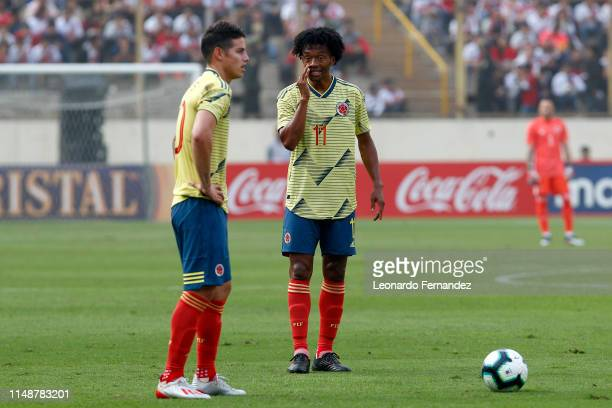 Juan Cuadrado of Colombia talks with his teammate James Rodriguez during a friendly match between Peru and Colombia at Estadio Monumental de Lima on...