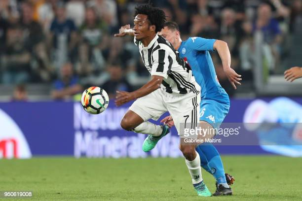 Juan Cuadrado of Juventus battles for the ball with Mario Rui of SSC Napoli during the serie A match between Juventus and SSC Napoli on April 22 2018...