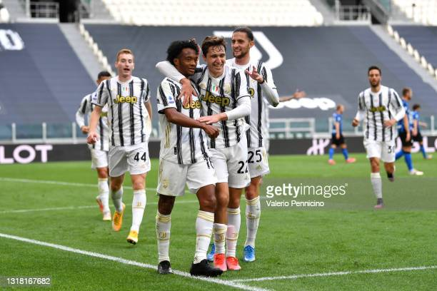 Juan Cuadrado of Juventus celebrates with team mate Federico Chiesa and Adrien Rabiot after scoring their side's second goal during the Serie A match...