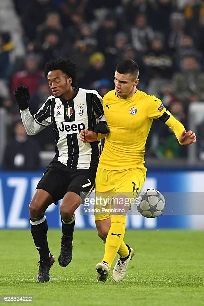 Juan Cuadrado of Juventus clashes with Amer Gojak of GNK Dinamo Zagreb during the UEFA Champions League Group H match between Juventus and GNK Dinamo...