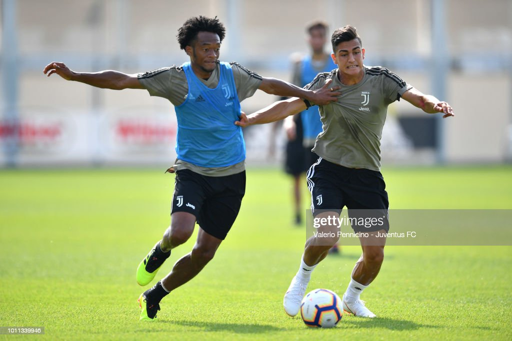 Juan Cuadrado (L) of Juventus competes during a training session at JTC on August 5, 2018 in Turin, Italy.