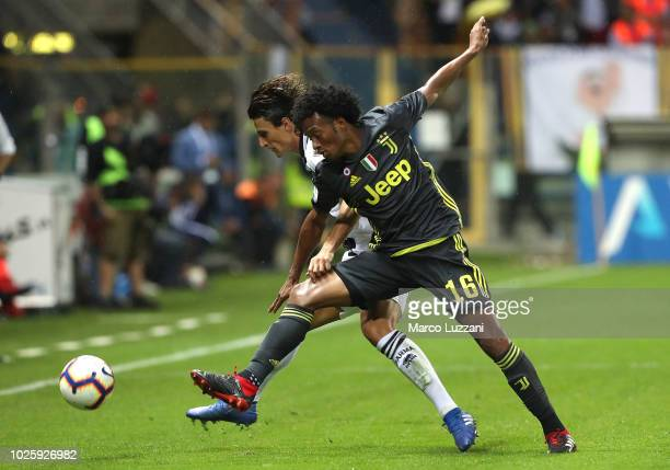 Juan Cuadrado of Juventus competes for the ball with Roberto Inglese of Parma Calcio during the serie A match between Parma Calcio and Juventus at...