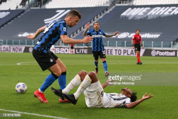 Juan Cuadrado of Juventus crashes to the ground to earn a late penalty after being challenged by Ivan Perisic of Internazionale during the Serie A...