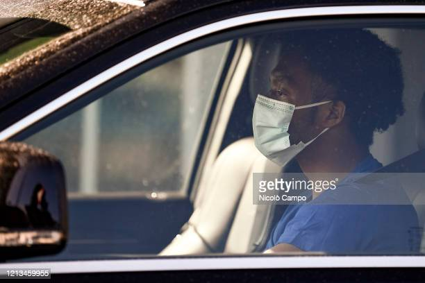 Juan Cuadrado of Juventus FC wearing a face mask arrives by car to the Continassa training ground to attend a training session Serie A plans to...