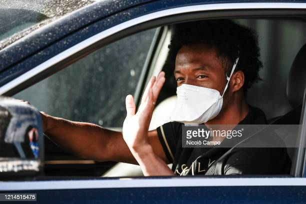 Juan Cuadrado of Juventus FC wearing a face mask waves as he arrives by car to the Continassa training ground to attend a training session Serie A...