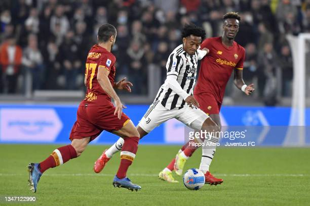 Juan Cuadrado of Juventus in action against Henrikh Mkhitaryan and Tammy Abraham of AS Roma during the Serie A match between Juventus and AS Roma at...