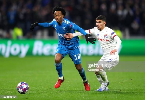 Juan Cuadrado of Juventus is challenged by Rayan Cherki of Olympique Lyon during the UEFA Champions League round of 16 first leg match between...