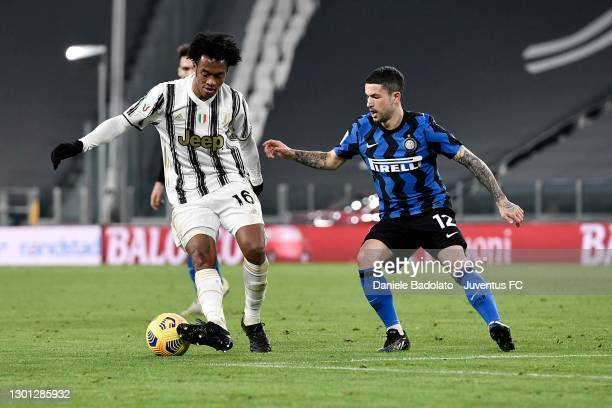Juan Cuadrado of Juventus is challenged by Stefano Sensi of FC Internazionale during the Coppa Italia semi-final Juventus and FC Internazionale at...