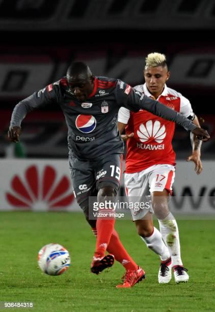 Juan Daniel Roa of Independiente Santa Fe struggles for the ball with Cristian Martinez Borja of America de Cali during a match between Independiente...