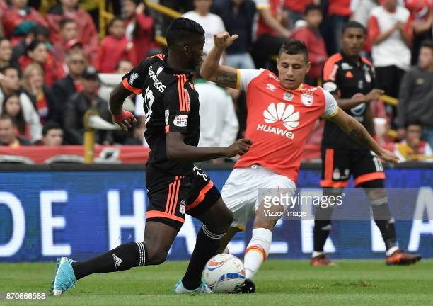 Juan Daniel Roa of Santa Fe struggles for the ball with Olmes Garcia of America during a match between Independiente Santa Fe and America de Cali as...