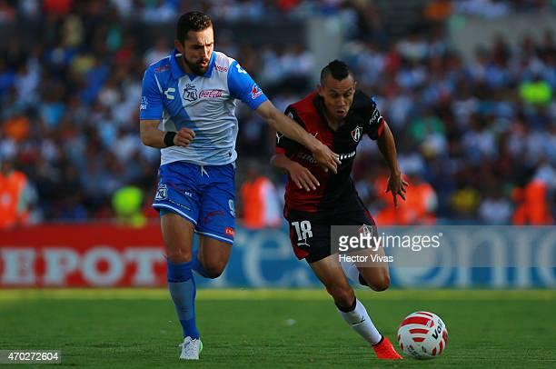 Juan de Dios Hernandez of Atlas struggles for the ball with Herculez Gomez of Puebla during a match between Puebla and Atlas as part of 14th round...
