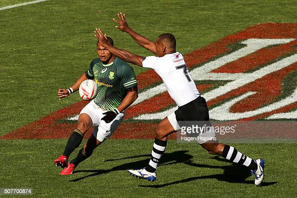 Juan de Jongh of South Africa has a kick charged down by Osea Kolinisau of Fiji during the 2016 Wellington Sevens cup semi-final match between South...