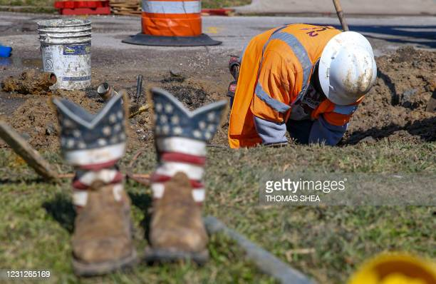 Juan De La Cruz works on a water pipe break at an intersection on February 19, 2021 in Galveston, Texas. - A fierce and deadly winter storm that...