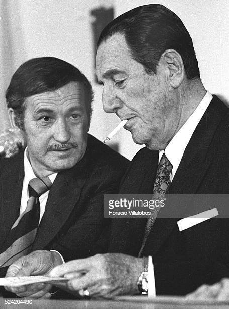 Juan Domingo Peron three times president of Argentina smokes a cigarette before speaking to Trade Union leaders next to secretary general Adelino...