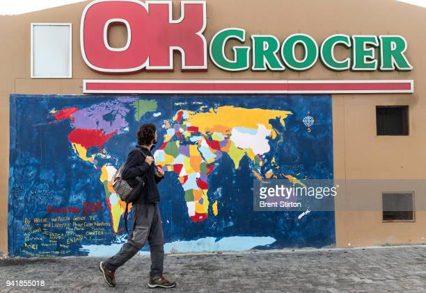 Juan exits a supermarket with a world map mural after buying a few supplies After a little mapwork and some notebook time Juan was off again on his...