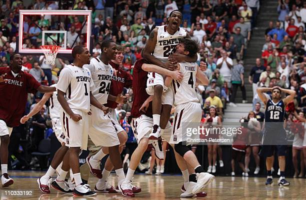 Juan Fernandez and Ramone Moore of the Temple Owls celebrate with teammates after defeating the Penn State Nittany Lions 66 to 64 in the second round...