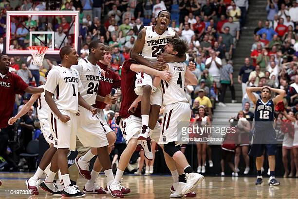 Juan Fernandez and Ramone Moore of the Temple Owls celebrates with teammates after defeating the Penn State Nittany Lions 66 to 64 in the second...