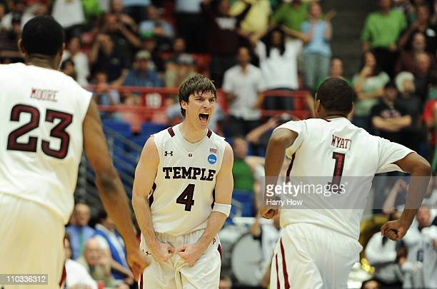Juan Fernandez celebrates with teammates Khalif Wyatt and Ramone Moore of the Temple Owls after he scored the winning basket to defeat the Penn State...