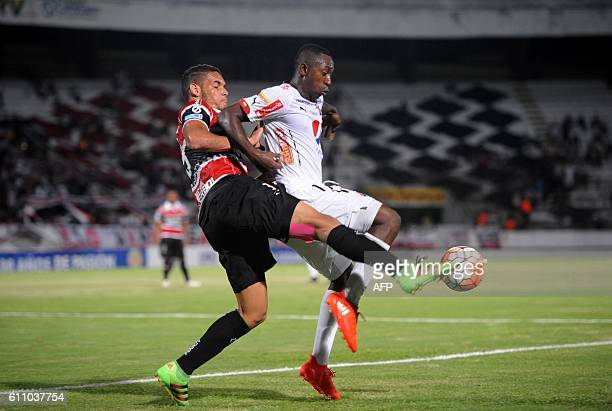 Juan Fernando Caicedo of Colombia's Independiente Medellin is marked by Neris of Brazil's Santa Cruz during their Sudamericana Cup football match in...