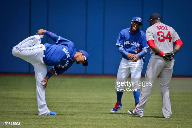 Juan Francisco and Jose Reyes of the Toronto Blue Jays and David Ortiz of the Boston Red Sox have a laugh together in the outfield before the...