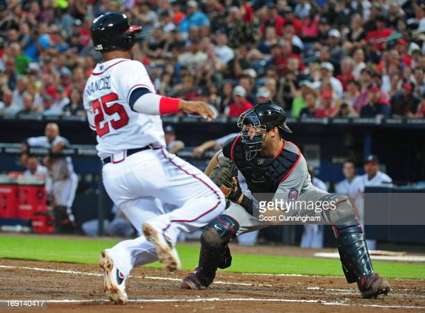 Juan Francisco of the Atlanta Braves scores on a fourth inning sacrifice fly against Joe Mauer of the Minnesota Twins at Turner Field on May 20 2013...