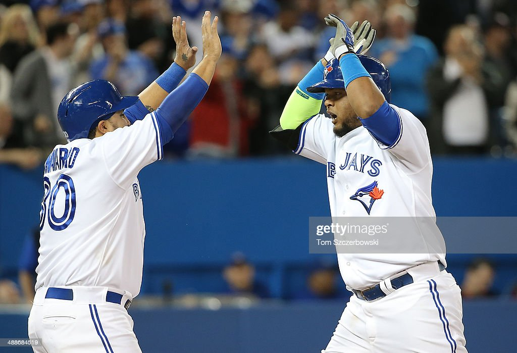 Juan Francisco #47 of the Toronto Blue Jays is congratulated by Dioner Navarro #30 after hitting a two-run home run in the seventh inning during MLB game action against the Philadelphia Phillies on May 7, 2014 at Rogers Centre in Toronto, Ontario, Canada.
