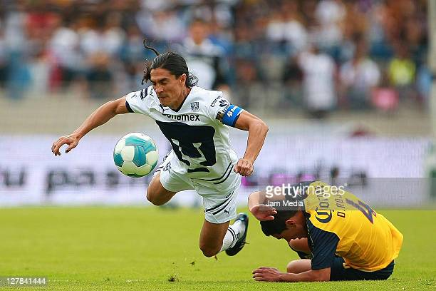 Juan Francisco Palencia of Pumas struggles for the ball with Oscar Rojas of America during a match as part of the Apertura 2011 at Olympic Stadium on...
