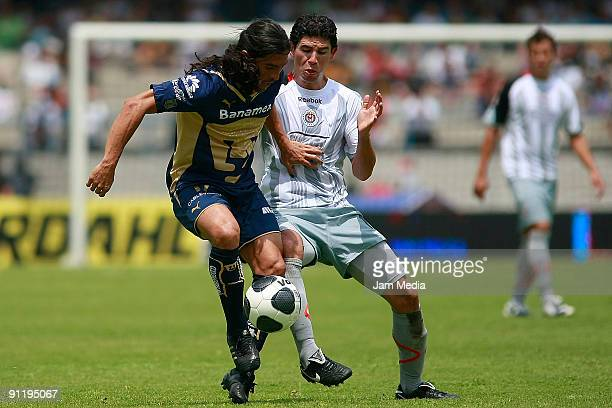 Juan Francisco Palencia of Pumas vies for the ball with Jonny Magallon of Chivas during their match at Azteca Stadium on September 27 2009 in Mexico...