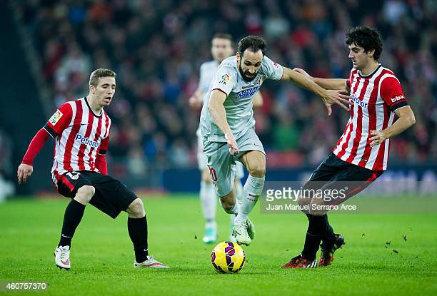 Juan Francisco Torres of Atletico de Madrid competes for the ball with Mikel San Jose of Athletic Club during the La Liga match between Athletic Club...