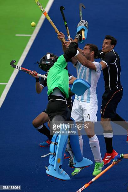 Juan Gilardi and Juan Vivaldi of Argentina defend a high ball against Germany for a looduring a Men's Preliminary Pool B match on Day 6 of the Rio...