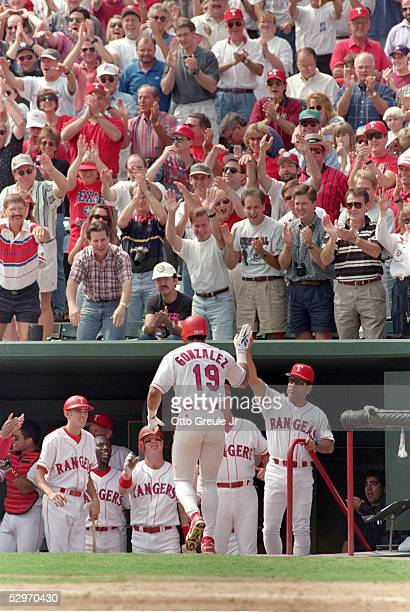 Juan Gonzalez of the Texas Rangers receives congratulations after hitting a home run during Game four of the American League Divisional Series...