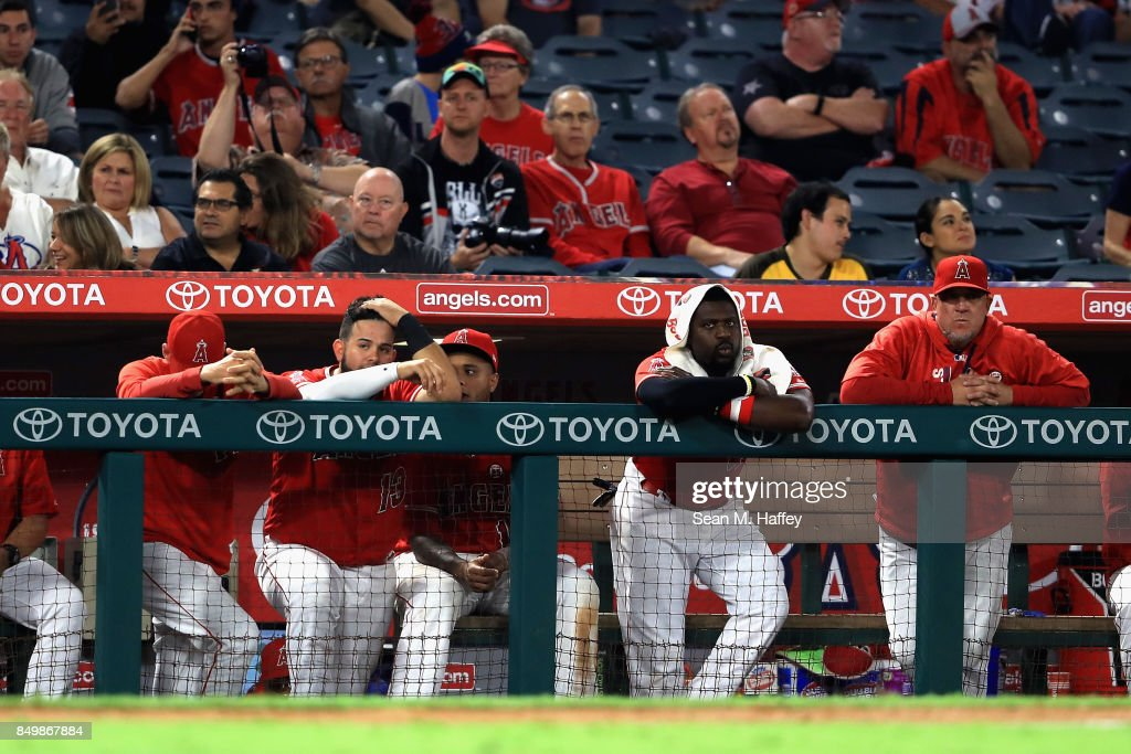 Juan Graterol #13 and Brandon Phillips #4 of the Los Angeles Angels of Anaheim look on from the bench during the ninth inning of a game against the Cleveland Indians at Angel Stadium of Anaheim on September 19, 2017 in Anaheim, California. The Cleveland Indians defeted the Los Angeles Angels of Anaheim 6-3.