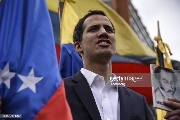 Juan Guaido president of the National Assembly holds the Venezuelan constitution while speaking during a proopposition rally in Caracas Venezuela on...