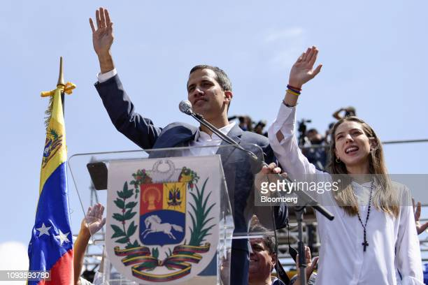 Juan Guaido president of the National Assembly who swore himself in as the leader of Venezuela and his wife Fabiana Rosales raise their hands during...