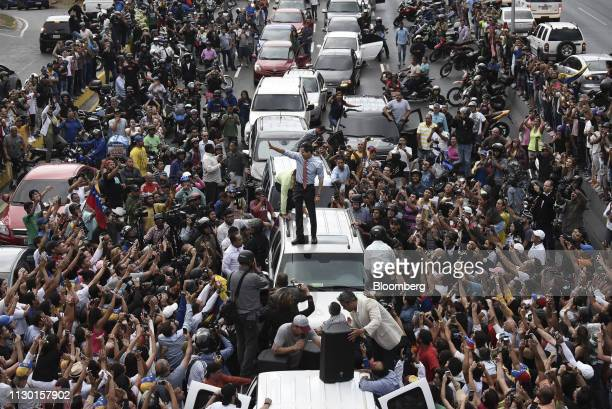 Juan Guaido, president of the National Assembly who swore himself in as the leader of Venezuela, center, stands on a vehicle during a protest against...