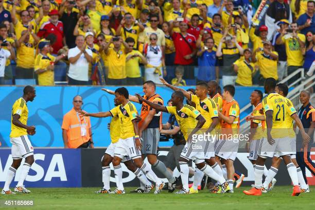Juan Guillermo Cuadrado of Colombia celebrates with teammates scoring his team's first goal after a penalty kick during the 2014 FIFA World Cup...