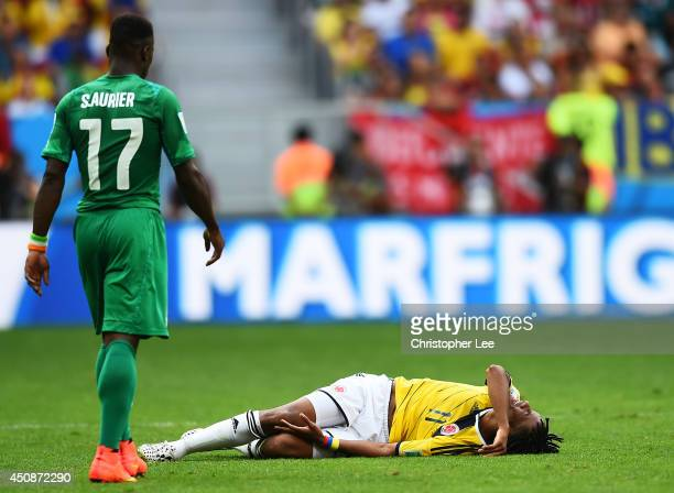 Juan Guillermo Cuadrado of Colombia lies on the pitch as Serge Aurier of the Ivory Coast walks on during the 2014 FIFA World Cup Brazil Group C match...