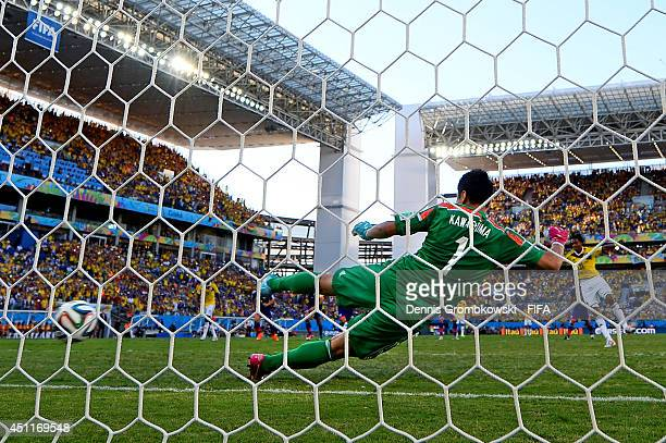 Juan Guillermo Cuadrado of Colombia scores his team's first goal from the penalty spot past Eiji Kawashima of Japan during the 2014 FIFA World Cup...